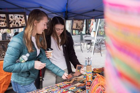 Two students look at bacon-themed merchandise at Pennsylvania Bacon Fest in downtown Easton, Pa.