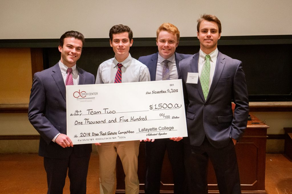 The winning students hold an oversized check at the Dyer Center's Real Estate Competition.