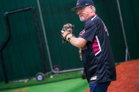 Chicago Cubs manager Joe Maddon gets ready to throw a baseball.