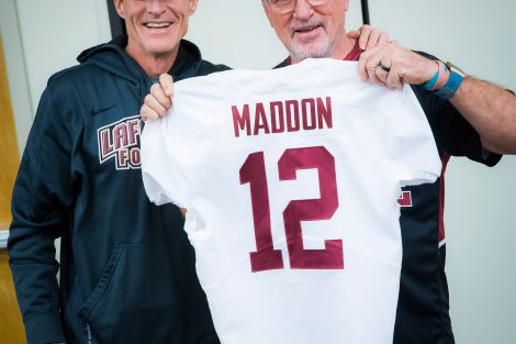 Chicago Cubs manager Joe Maddon '76 holds a football jersey with his name on it while Lafayette football coach John Garrett stands with him.
