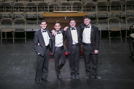 four male choir members stand in a line on stage