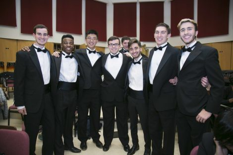 eight male choir members stand in a line