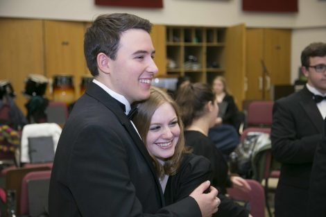 two student choir members hugging