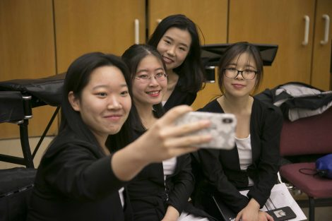 four students pose for a selfie