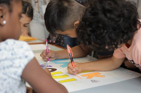 Local third-graders use markers to create letters on a poster during a class taught by Lafayette College students in the Happiness First-Year Seminar.