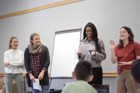 Students explain the rules to mad libs to a group of elementary students.