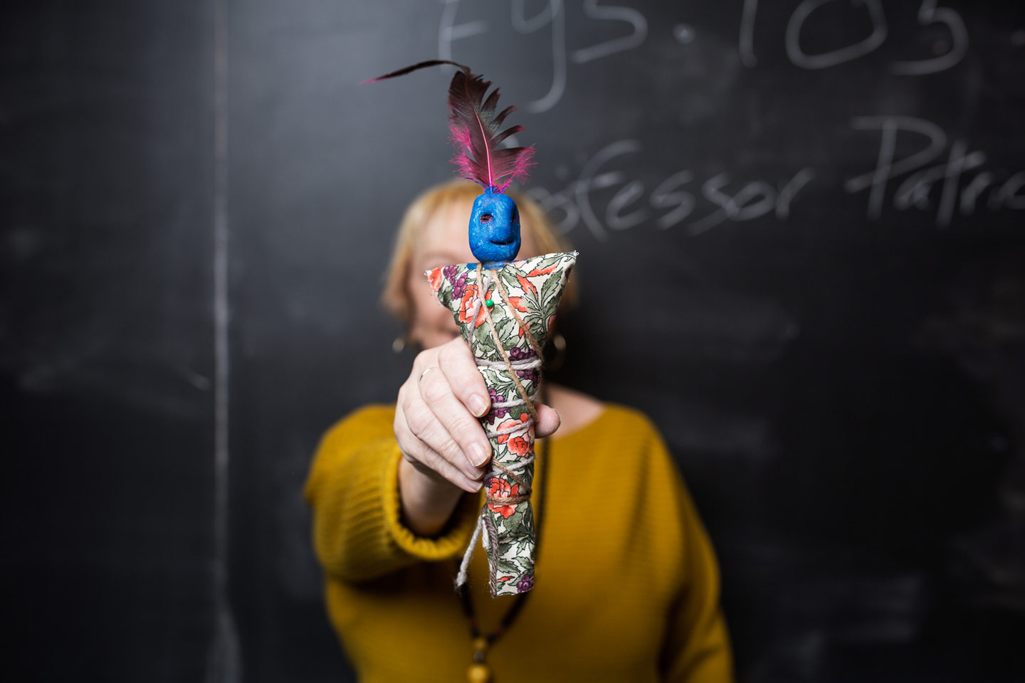 English Professor Pat Donahue holds a voo-doo doll at the front of her classroom blackboard.