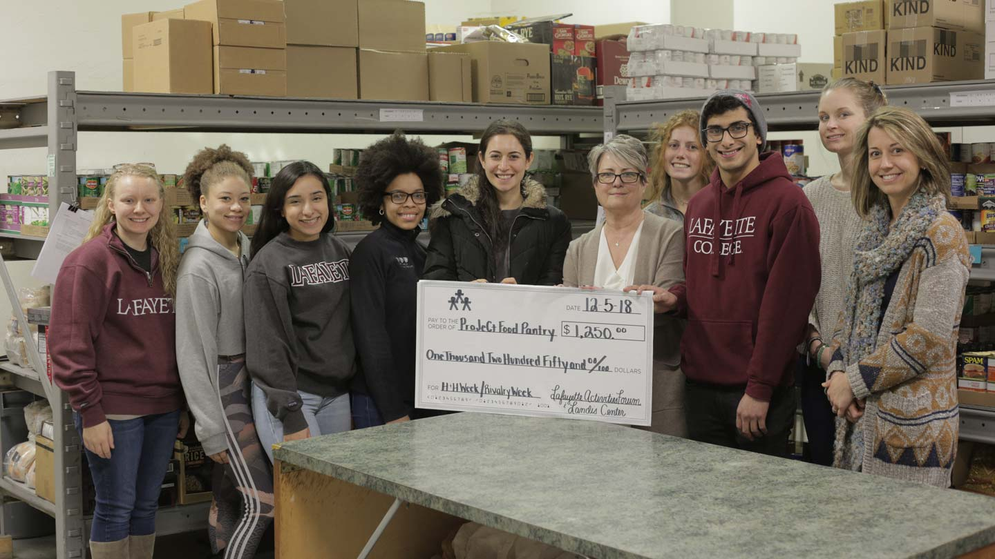 A group photo with an oversized $1,250 check for ProJeCt Food Pantry