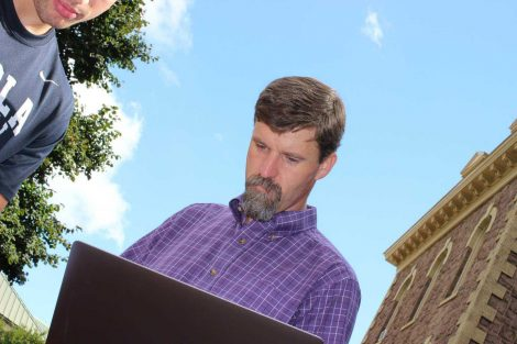 Professor looks at his laptop during the Center for Community Engagement program.