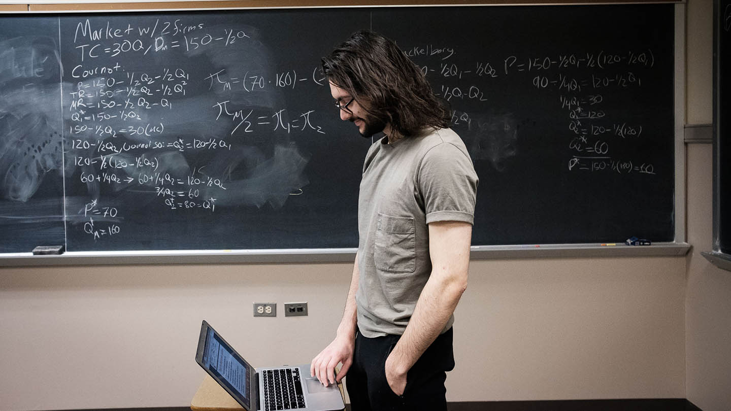 A student studies and uses the chalkboard behind him.