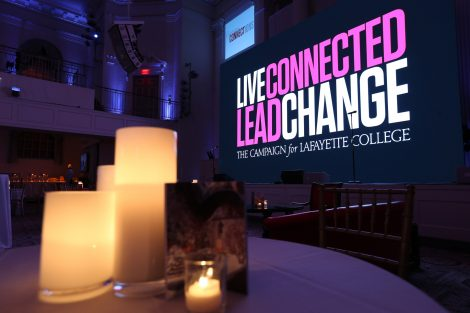 A screen projects 'Live Connected, Lead Change' at the annual holiday party in New York City.