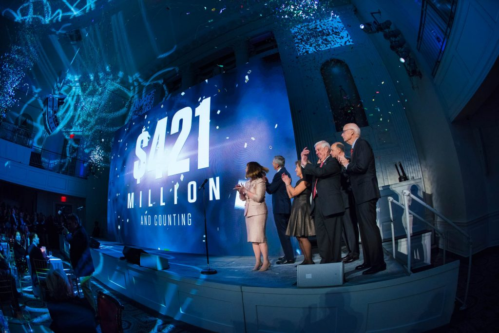 President Alison Byerly and others stand on stage at the annual holiday party in New York City.