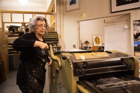 MaryAnn Miller works on the printmaking press at Lafayette College's Experimental Printmaking Institute.