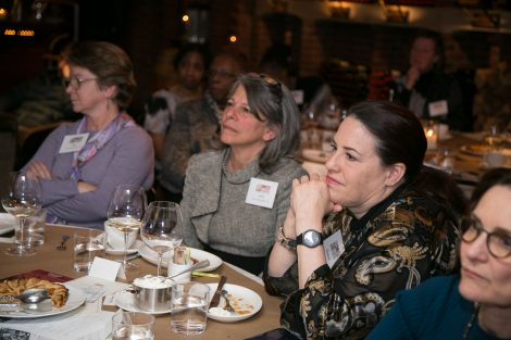 Women seated at a table listen to a speaker . at the First Women of Lafayette brunch in New York on Dec. 1.