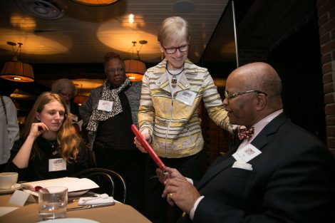 Riley Temple hold a book and talks with an alumna at the First Women of Lafayette brunch in New York on Dec. 1.