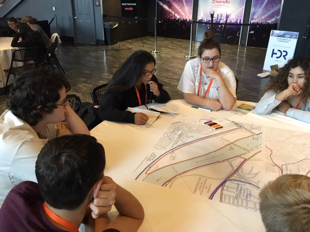 Students talk around a table at the brownfields conference.