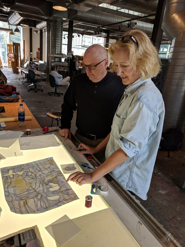 Professor Ed Kerns and Kim Malm '90 look at one of her paintings on a light table.