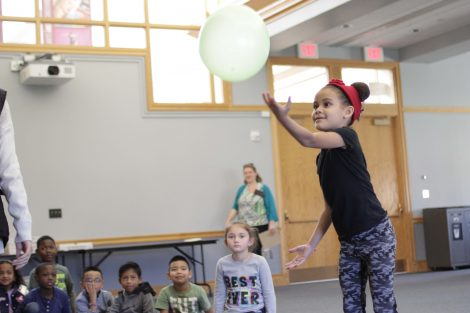 Elementary student demonstrates how easy it is to keep one balloon in the air.