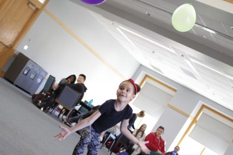 Elementary student realizes keeping two balloons in the air is harder.