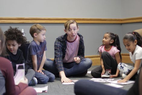 Lafayette student gathers elementary students around their colored pages.