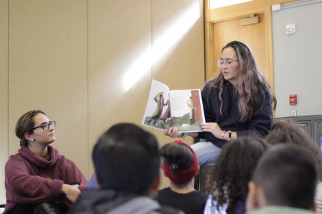 Lafayette student reads the book Stone Soup to a group of elementary students.