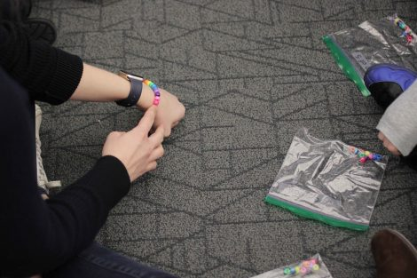 Elementary students see the beaded bracelet they will make after sharing beads.
