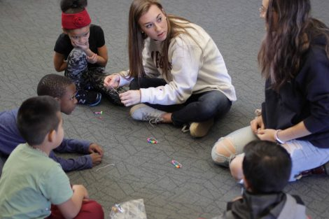 Lafayette students help elementary students make bracelets.