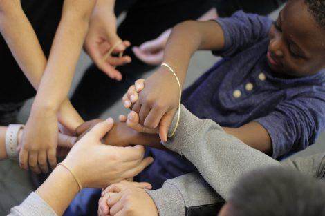 Elementary students get their wrists rubber banded together.