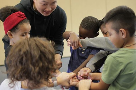 Lafayette student helps rubber band elementary student wrists.