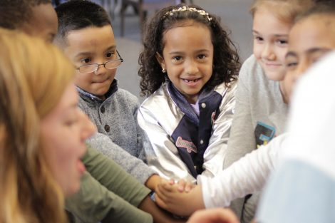 Elementary students smile with wrists rubber banded.