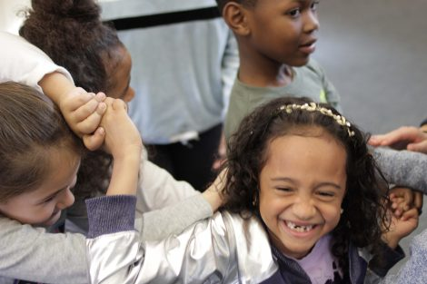 Elementary students laugh as they get untangled.