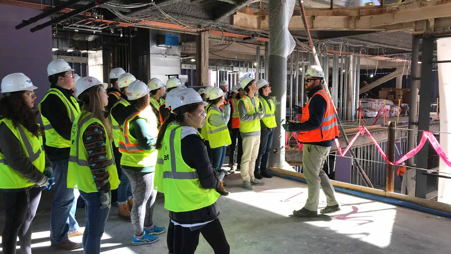 A construction worker gives Lafayette College students a tour of Rockwell Integrated Sciences Center.