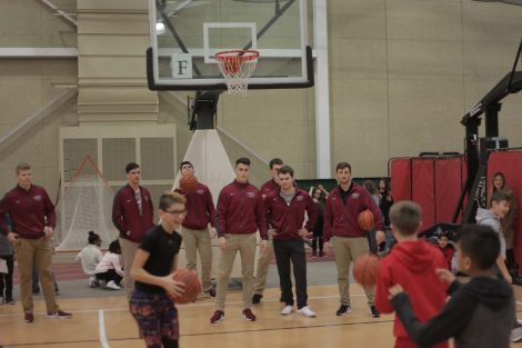 Fifth graders take turns shoot baskets with Lafayette athletes.
