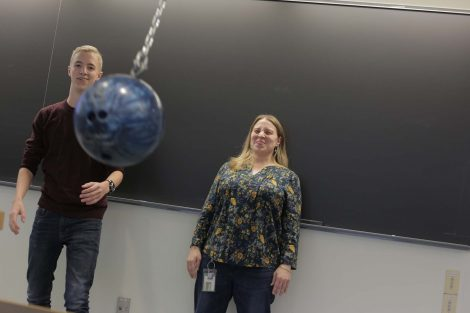 The teacher smiles after narrowly escaping a bowling ball that could have smashed her face.