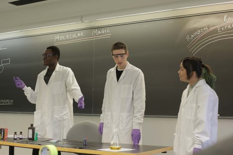 Lafayette students point at the yellow liquid in the beaker.