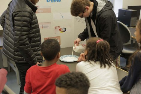 Lafayette students pours milk onto plate.