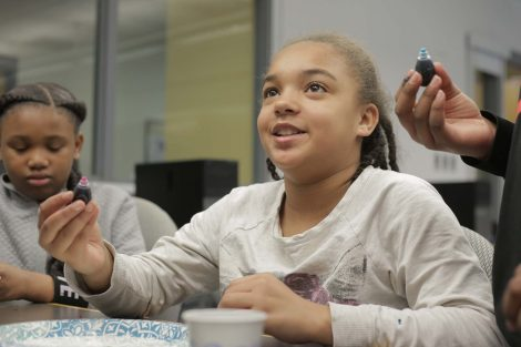 Fifth grader adds food coloring to her plate of milk.
