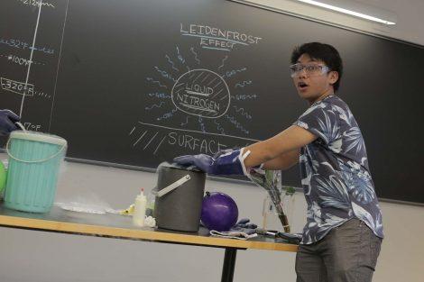 Lafayette students pushes green balloon into liquid nitrogen.