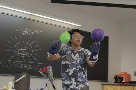 Lafayette student pulls green and purple balloon out of the liquid nitrogen.