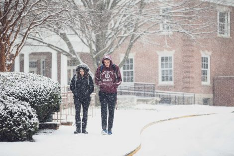 students walk looking cold in the snow