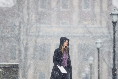 a student walks in front of markle in the snow