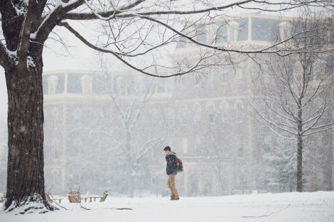a student walks in front of pardee in the snow