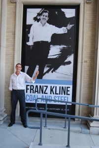 Art history professor Bob Mattison in front of a poster for the Franz Kline exhibit