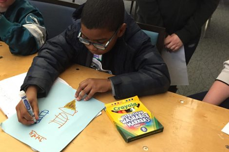 A child uses magic marker to draw a picture on paper.