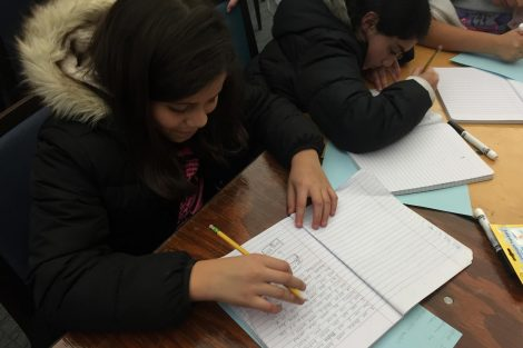 Cheston Elementary School children write in their notebooks.