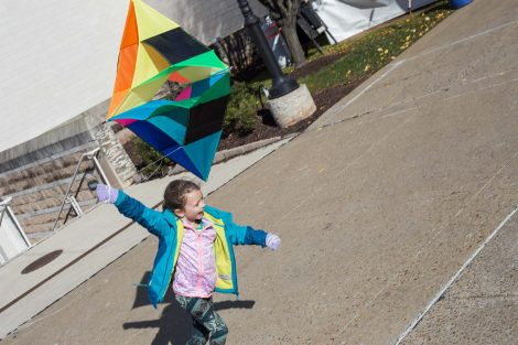 Second grader runs with a kite trailing behind her.
