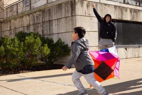 Second grade boy starts running with the kite while a Lafayette student encourages him to lift it up.