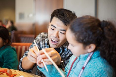 Lafayette student teaches a second grader how to hold chop sticks.