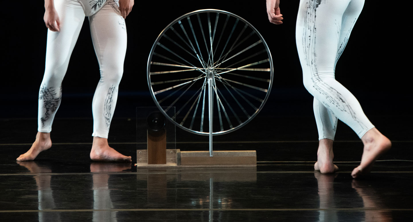 A view of a wheel and the legs for two Taylor 2 Dance dancers performing on stage at Lafayette College's Williams Center for the Arts
