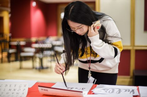 A student writes calligraphy at the Lunar New Year celebration.